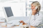 Side view of a smiling female doctor using phone and computer at desk in medical office