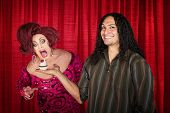 stock photo of drag-queen  - Smiling latino man with hungry drag queen and cupcake - JPG