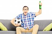 Excited male sport fan with soccer ball and beer watching sport isolated on white background