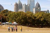 People Fly Kites In Park Against Atlanta City Skyline
