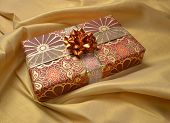 A decorative gift box against a golden drapery background