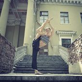 Attractive teen girl dancing outdoor in park against old building with columns. Toned.