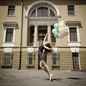 Attractive teen girl dancing with balloons outdoor against old building. Vintage toned.