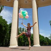Attractive teen girl dancing outdoor in park against columns with balloons.
