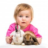 baby girl in a pink T-shirt with two small  rabbits isolated on white background