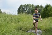 Barefoot Boy Runs Through A Puddle.