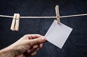 Hand Picking Blank Note Paper Attached To Rope With Clothes Pins