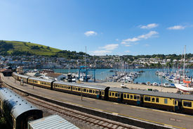 stock photo of dartmouth  - Dartmouth and Kingswear train station with colourful yellow carriages on railway track by marina with boats with blue sky and clouds in Devon England UK - JPG