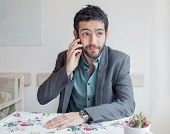 Young man wearing jacket sitting in restaurant and talking on phone.