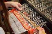 Woman working at the loom. Russian national crafts.