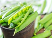 stock photo of snow peas  - green pea on the wooden board and on a table - JPG
