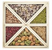 triangles and squares abstract  - a variety of beans and lentils in an isolated wooden tray