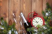 Christmas wooden background with clock, champagne, snow fir tree and copy space