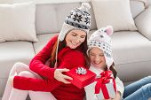 Mother and daughter exchanging gifts at christmas at home in the living room
