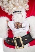 Santa holding jar full of pennies on white background