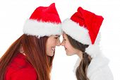 Festive mother and daughter smiling at each other on white background