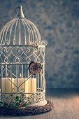 Festive candles in birdcage with joy decoration