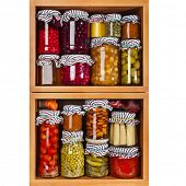 many glass bottles with preserved set food in wooden cabinet