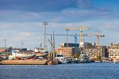 Coastal Cityscape Of Modern Helsinki With Cranes And Ships