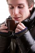 Young Man Having A Hot Drink In Winter