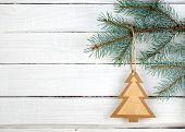 Paper Christmas Tree On Spruce Branch On Wooden Background