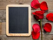 Blackboard And Red Rose On Wooden Background