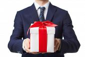 Businessman in suit holding giftbox tied by red ribbon