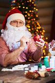 Senior man in Santa cap and beard painting toy ball and looking at camera