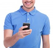 cropped picture of a young casual man playing on his telephone and smiling. isolated on a white background