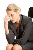Depressed businesswoman sitting on armchair.