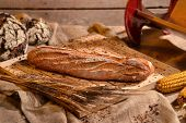 Rustic bread and wheat on an old vintage wood table and chest.