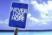 Never Lose Hope sign with a beach on background
