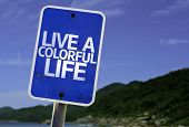 Live a Colorful Life sign with a beach on background