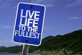Live Life to the Fullest sign with a beach on background