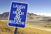 Laugh As Much As You Breathe sign with a desert background