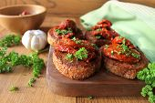 Appetizer- bruschetta with olive oil, sun-dried tomatoes and parsley