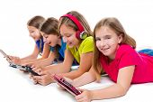 sisters cousins kid girls with tech tablets and smartphones in a row lying on white background