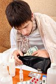 stock photo of home remedy  - Sick Teenager checking the Wallet on the Sofa at the Home - JPG