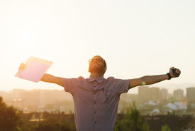 image of celebrate  - Successful professional casual man celebrating work success and raising arms against city background on sunset - JPG
