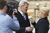 stock photo of interview  - Female Journalist With Microphone Interviewing Businessman Outdoors - JPG