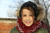 pic of auburn  - Preschool girl with auburn hair and brown eyes is playing with snow outside in a winter day - JPG