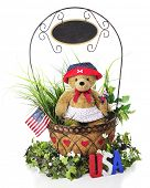 stock photo of greenery  - A basket full of greenery and a toy bear in patriotic attire - JPG