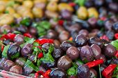 foto of pimiento  - Close up view of black olives seasoned with red pepper and parsley - JPG