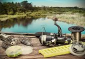 picture of spinner  - fishing tackle on a pontoon on the background of the lake in the woods - JPG