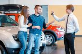 Sales consultant gives keys from new car to young couple poster