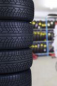 stock photo of four-wheel drive  - Closeup of a pile of four black tires in the spare parts store - JPG