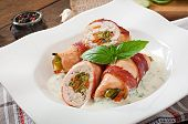 foto of bacon strips  - Delicious chicken rolls stuffed with green beans and carrots wrapped in strips of bacon with yoghurt and basil sauce - JPG