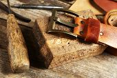 picture of leather tool  - Craft tools with leather belt on table close up - JPG