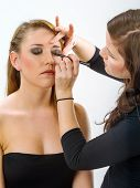 picture of makeup artist  - Photo of a professional makeup artist applying eye makeup onto a blond model - JPG