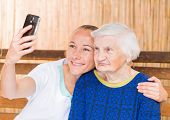 stock photo of geriatric  - Elderly woman with her caregiver taking a selfie photo - JPG
